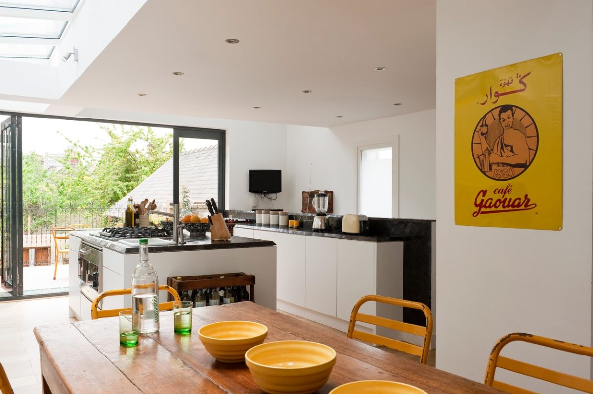 Modern kitchen with large island unit, tuscan wooden dining table, yellow metal dining chairs and fr