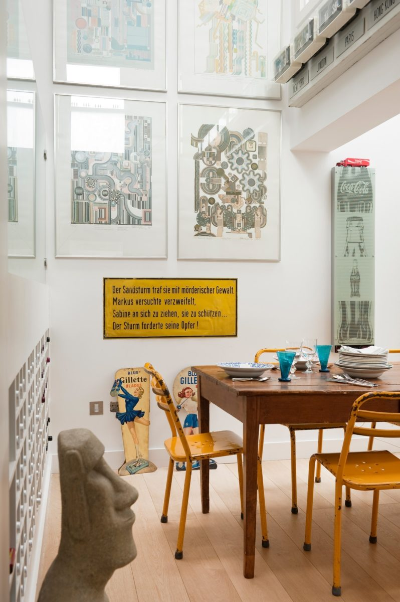 Yellow metal chairs around wooden dining table in kitchen with Eduardo Paolozzi prints, Bazon Bock a