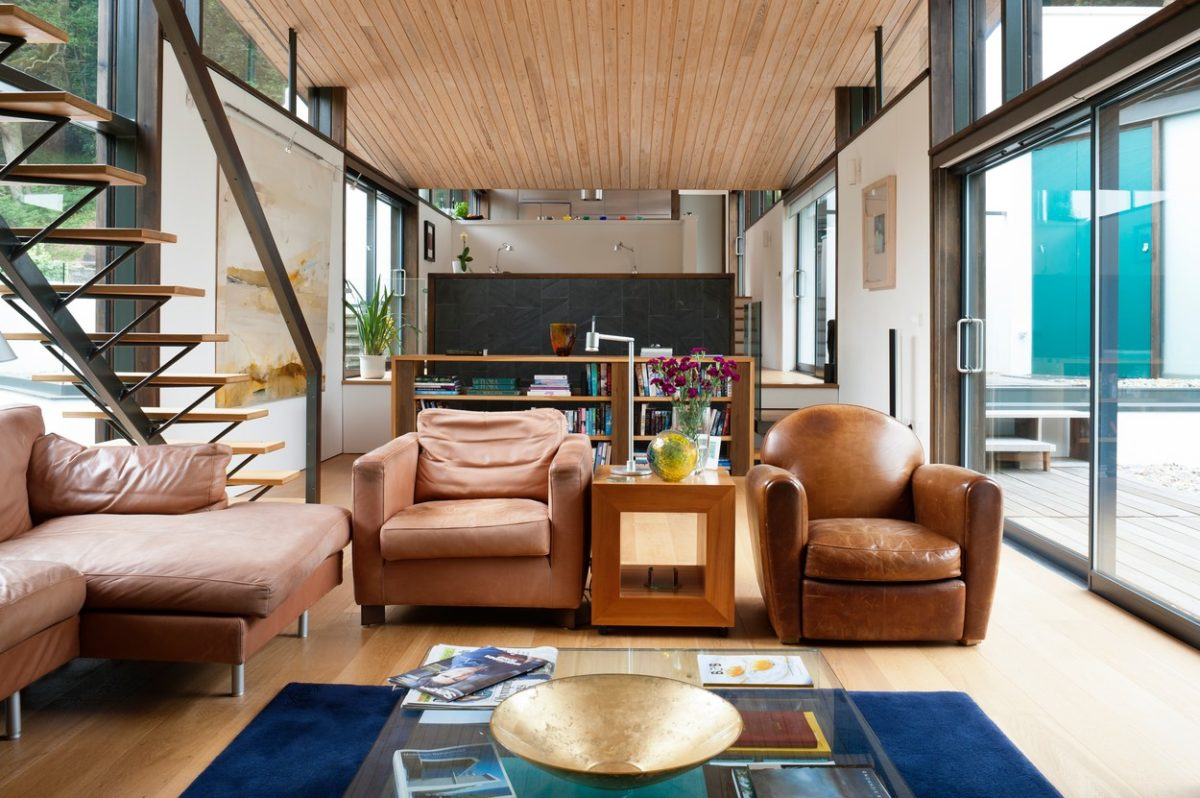 Leather armchairs in open plan living space with wood clad ceiling and cantilevered staircase